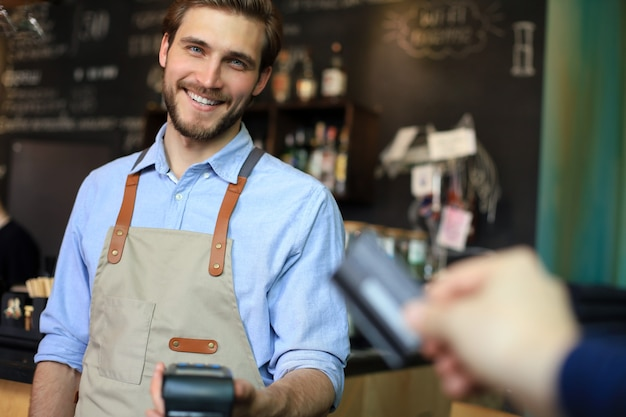 Customer using credit card for payment to owner at cafe restaurant, cashless technology.