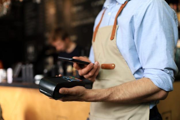 카페 레스토랑에서 주인에게 지불하기 위해 신용 카트를 사용하는 고객, 현금 없는 기술 및 신용 카드 지불.