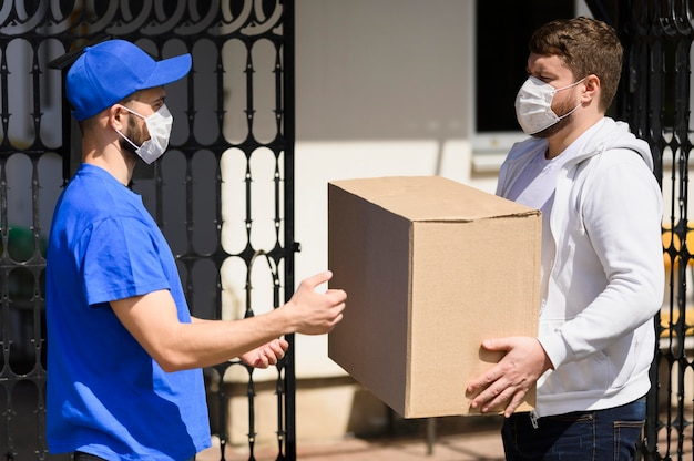 Customer with face mask receiving parcel from delivery man
