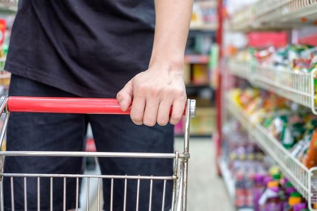 Покупатель с корзиной, выбирая продукт в супермаркете