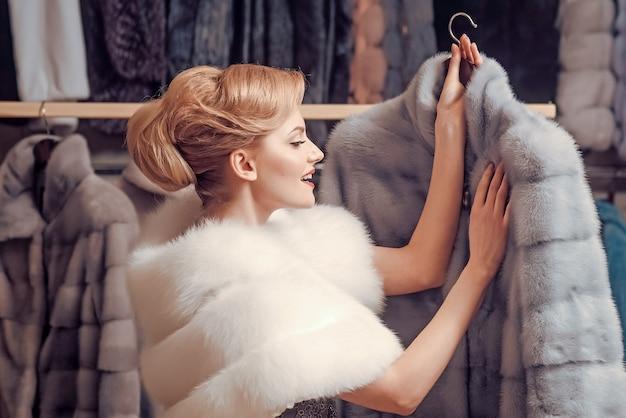Женщина покупателя покупает меховое пальто. концепция моды и покупок.