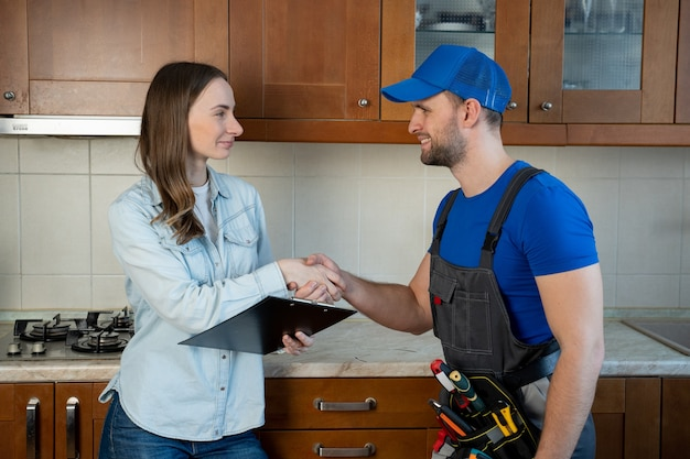 Customer woman signing invoice from male plumber standing in kitchen