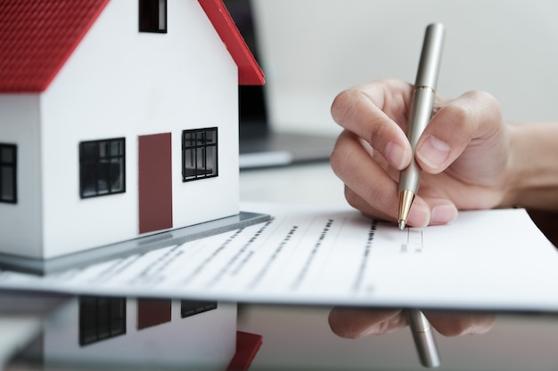 顧客は不動産取引に署名するためにローンや保険契約の文書を読んでいます