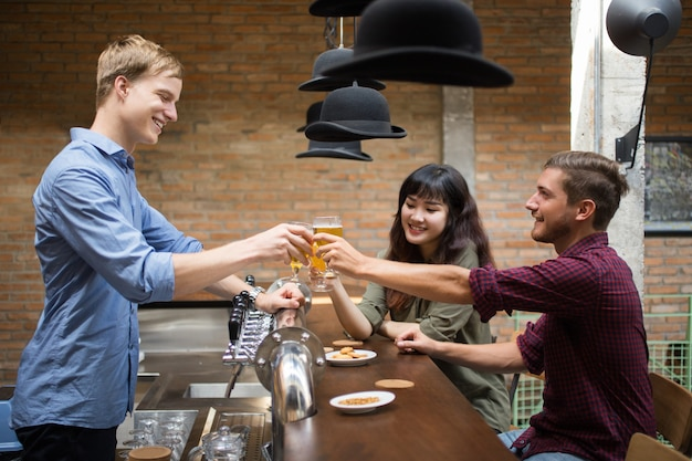 Customers and bartender toasting at pub counter