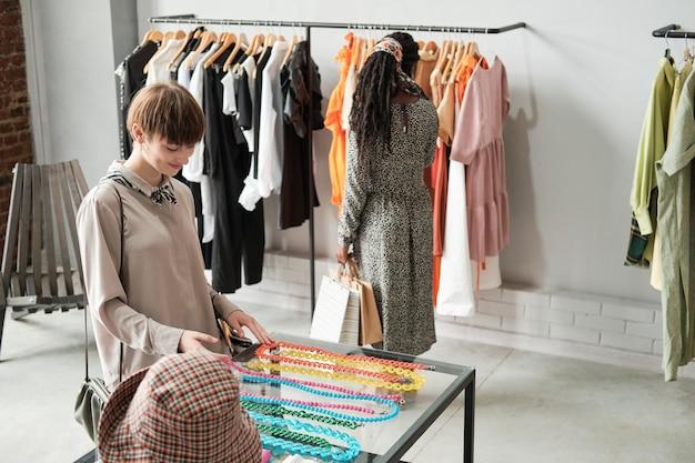 Покупатели покупают новую одежду и аксессуары в торговом центре.