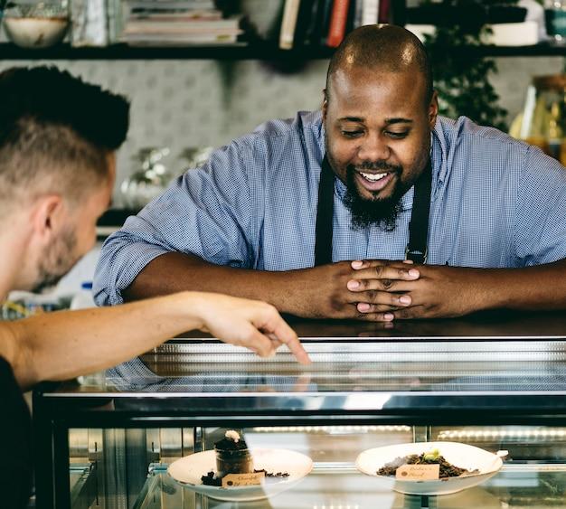 Customers choosing cake at the display fridge