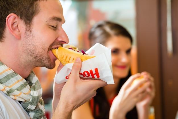 Customers eating hotdog in fast food snack bar
