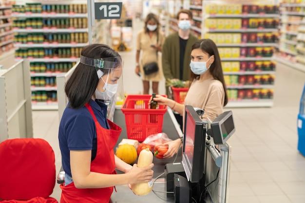 スーパーマーケットのチェックアウトキューにいる顧客は、マスクを着用し、covid-19検疫時間中に社会的距離のルールに従います