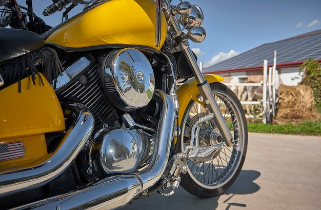 屋外航海中の田園風景にクロムメッキの駐車場を備えた、カスタマイズされた黄色のオートバイ。