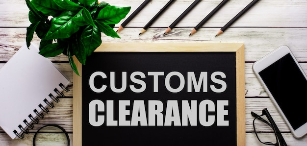 Customs clearance는 전화, 메모장, 안경, 연필 및 녹색 식물 옆에있는 검은 색 보드에 흰색으로 표시됩니다.