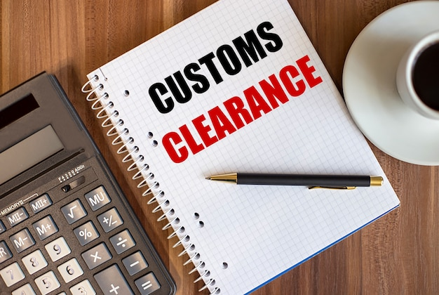 Customs clearance written in a white notepad near a calculator and a cup of coffee on a dark wooden surface.