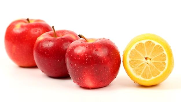 白い背景にレモンと3つのリンゴをカットします。有用なビタミン食品