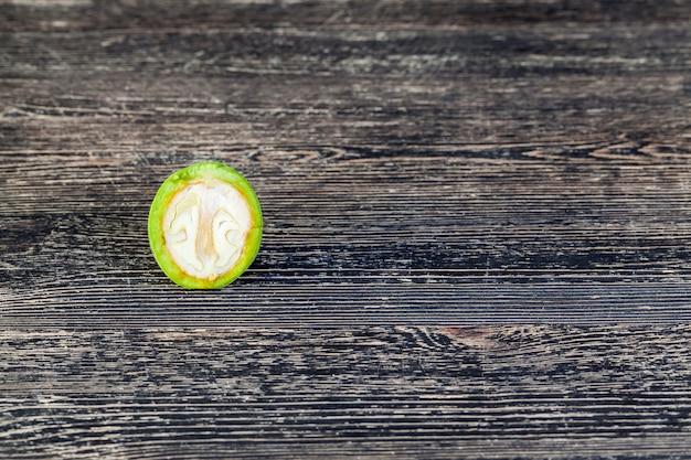 Разрезанный и сломанный кусок незрелого зеленого грецкого ореха на черном столе