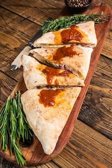 뜨거운 토마토 소스를 곁들인 나무 보드에 햄과 치즈를 곁들인 칼 조네 마감 피자를 자르고 슬라이스했습니다. 나무 배경입니다. 평면도.