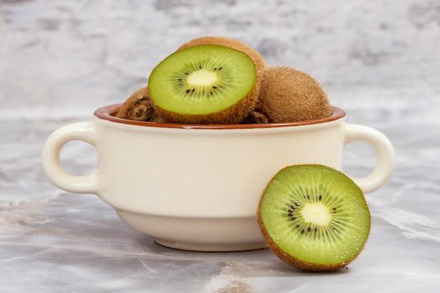 회색 돌 식탁에 있는 도자기 그릇에 키위 과일을 자르고 통째로 넣으세요. 건강한 음식.