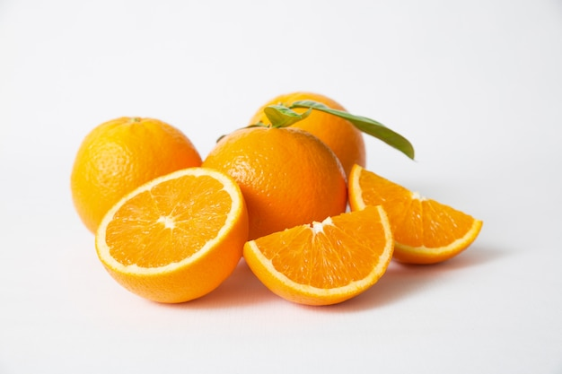 Нарезанные и целые оранжевые фрукты с зелеными листьями