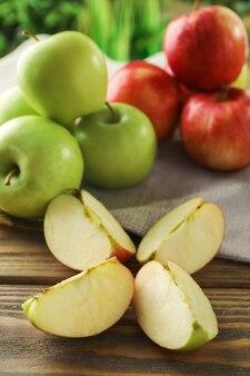 木製のテーブルで完熟した新鮮なリンゴをカットして丸ごと
