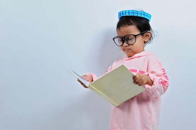 アジアの女の子が眼鏡をかけてカットし、本を開いて、灰色の背景に真剣に隔離された本を読む