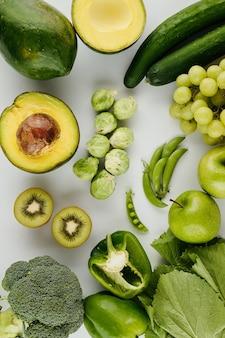 회색 식탁에 아보카도, 브뤼셀 콩나물, 키위, 후추 및 기타 야채와 과일을 자릅니다.