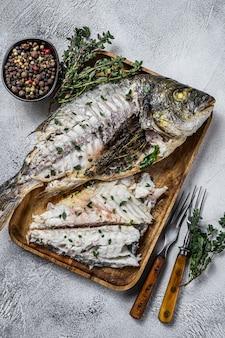 Запеченную рыбу дорадо из морского леща нарезать на деревянном подносе. белый фон. вид сверху.