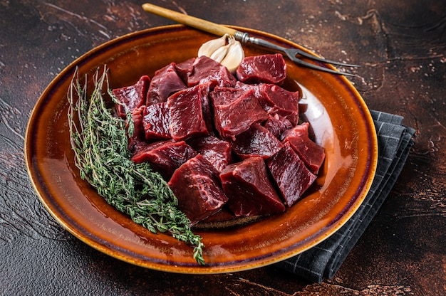 牛肉または子牛の生の心臓をハーブの入った素朴な皿に切ります。上面図。