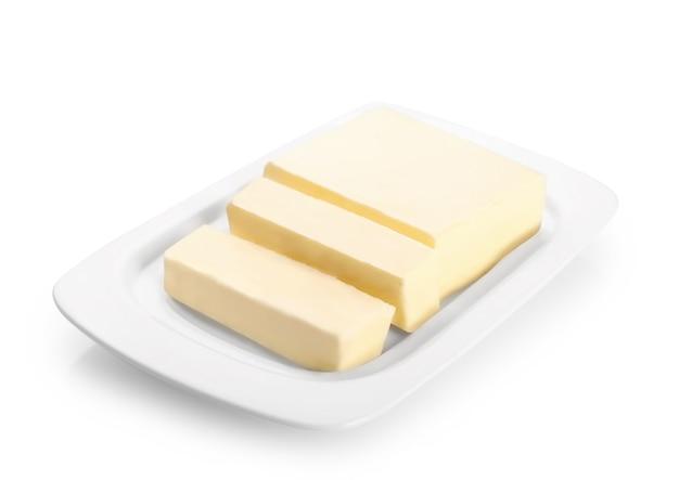 白に分離された白いセラミックバター皿に新鮮なバターのブロックをカット