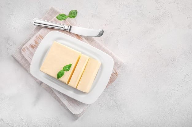 白の白いセラミックバター皿に新鮮なバターのブロックをカットします