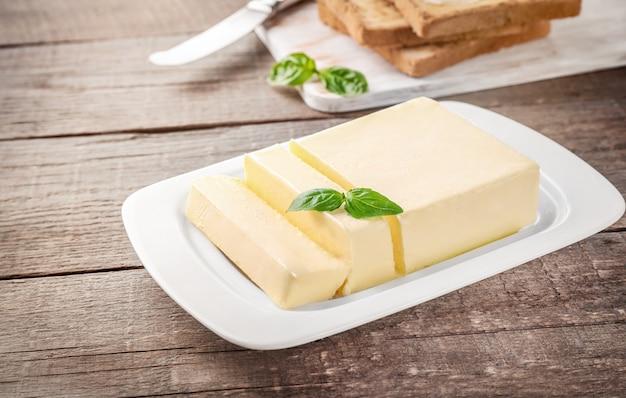 木製の白いセラミックバター皿に新鮮なバターのブロックをカットします