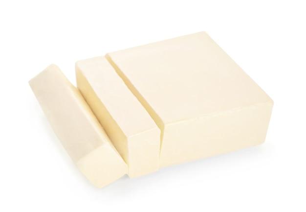 白で分離された新鮮なバターのカットブロック