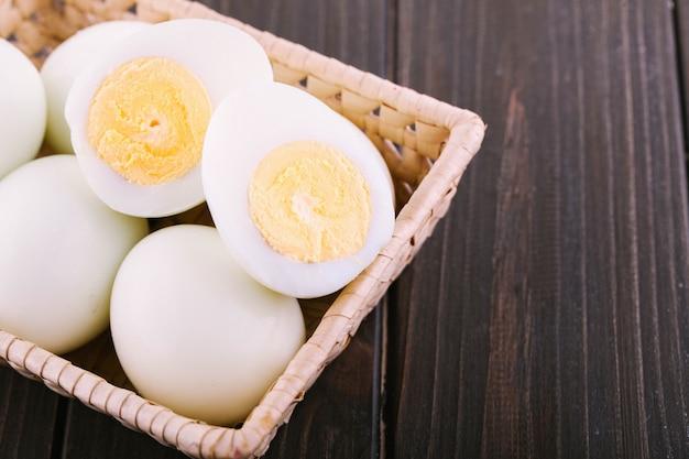 Cut boiled eggs lie in wooden besket on dark dinner table