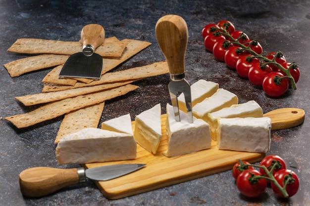Нарезать сыр бри на разделочной доске рядом с помидорами и лепешками