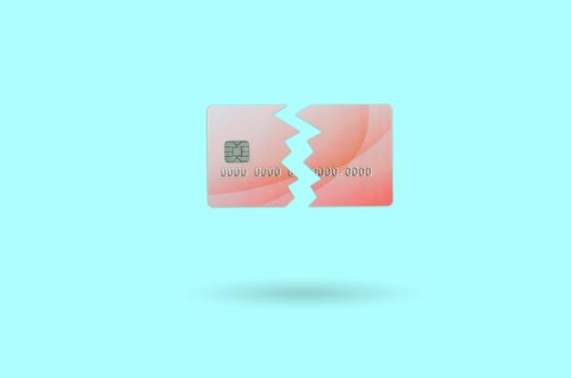 青に分離された壊れた赤いクレジットカードをカットします。