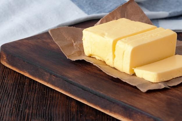 Разрежьте масло на тарелку с синим полотенцем на кухонном столе
