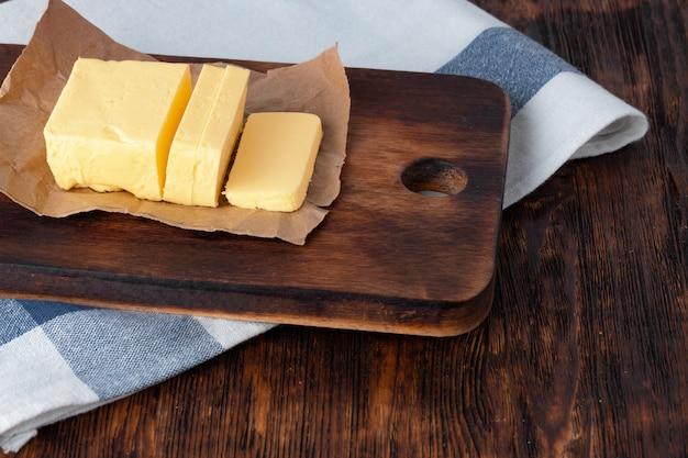 キッチンテーブルの上の青いタオルでプレートにバターをカットします。