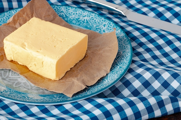 Cut butter on plate with blue towel on kitchen table
