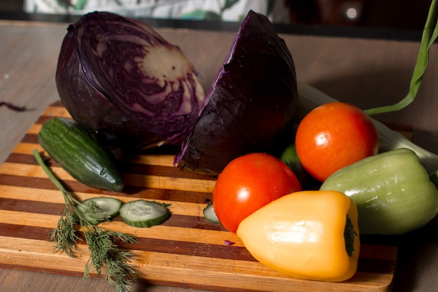Cut cabbage and sliced cucumbers with tomatoes and peppers on a board on the kitchen table Premium Photo