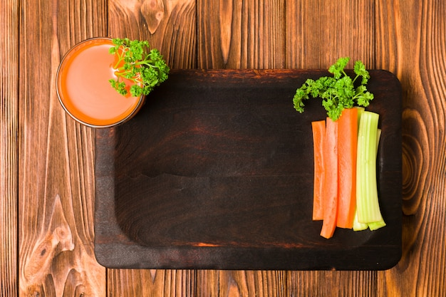 Cut carrot and celery with orange fresh juice and parsley leaves on kitchen board with copy space