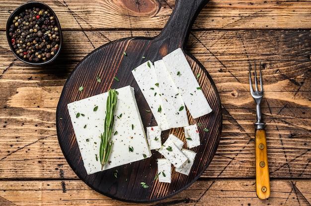 Нарезать сыр фета с розмарином на деревянной разделочной доске. деревянный фон. вид сверху.