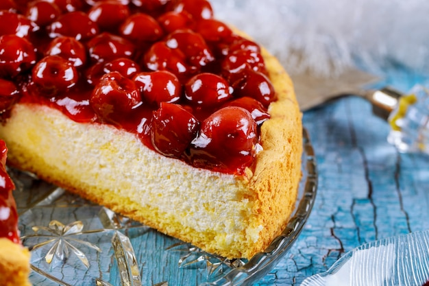 Cut cheesecake with cherry jelly decorated on the top
