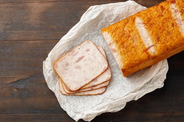 Нарезать кусочками куриную колбасу на деревянном столе