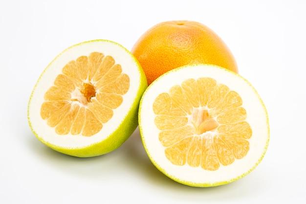 白い背景の上の柑橘類のグレープフルーツの果実をカットします。