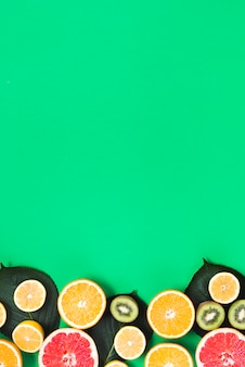 Cut of colorful fresh tropical fruits on green background