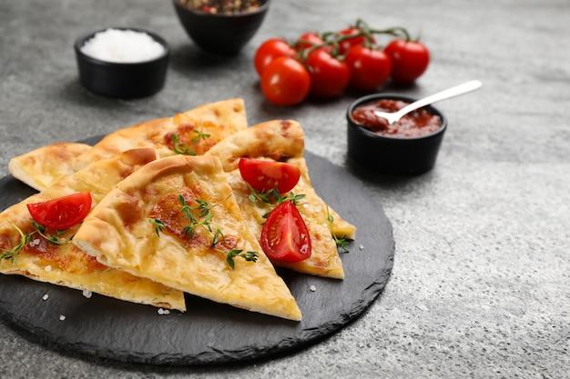 グレーのテーブルの上でチーズ、タイム、トマト、ソースでおいしいハチャプリをカットします