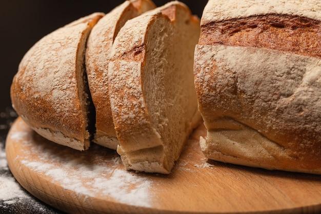 테이블에 신선한 빵을 자르고 나무 보드에 빵 조각을 자르십시오.