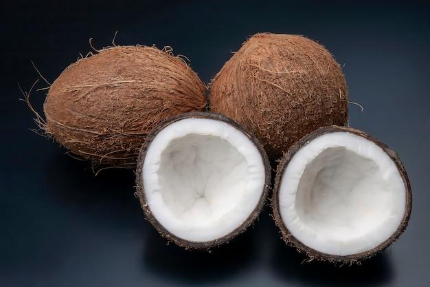 어두운 배경에 신선한 코코넛을 자르십시오. 비타민 과일. 건강한 음식