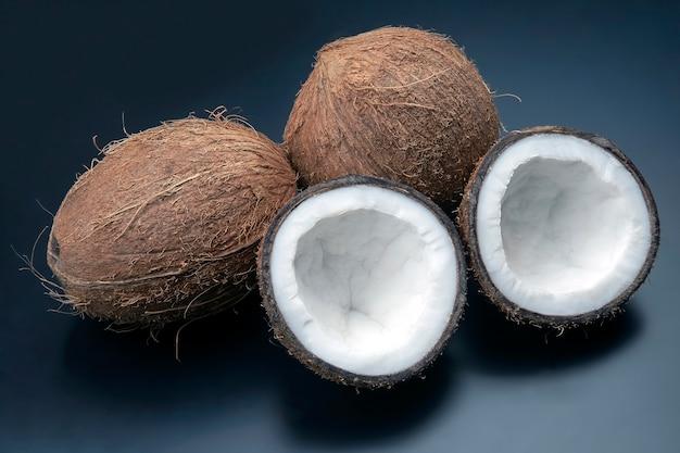 어두운 공간에서 신선한 코코넛을 자릅니다. 비타민 과일. 건강한 음식