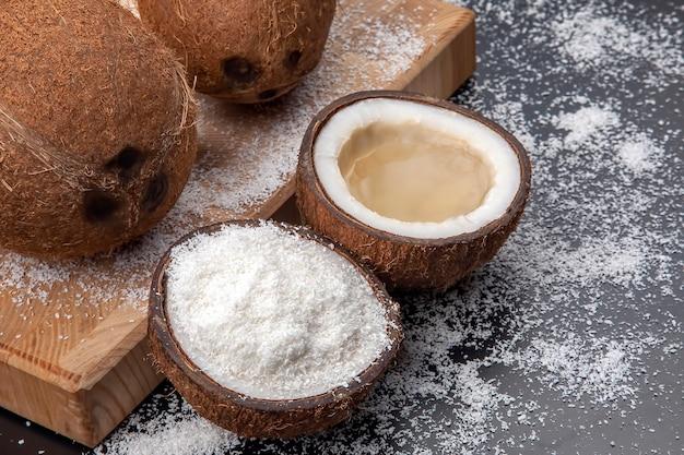 코코넛 플레이크의 어두운 배경에 실제 코코넛 밀크로 신선한 코코넛을 자릅니다. 비타민 과일. 건강한 음식