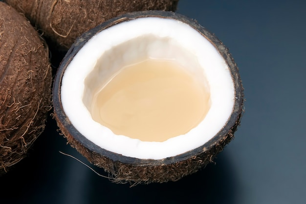 어두운 배경에 진짜 코코넛 밀크로 신선한 코코넛을 자릅니다. 비타민 과일. 건강한 음식