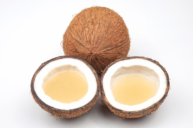 白い背景の上に本物のココナッツミルクで新鮮なココナッツをカットします。ビタミンフルーツ。健康食品