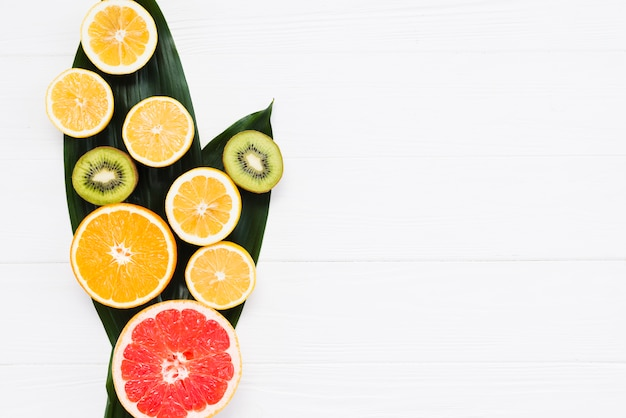 Cut of fresh exotic fruits on banana leafs on white background